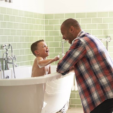 Man bathing his son in a clean bathroom